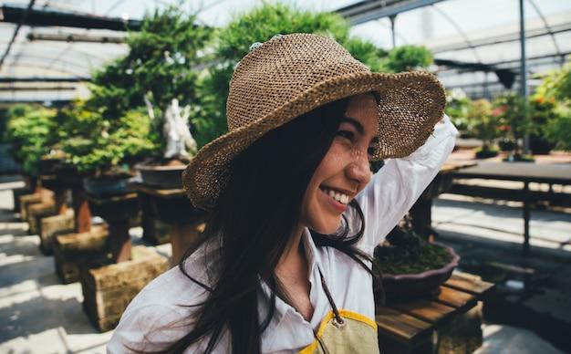 Bonsai gewächshaus zentrum. reihen mit kleinen bäumen, frau arbeitet und kümmert sich um die pflanzen