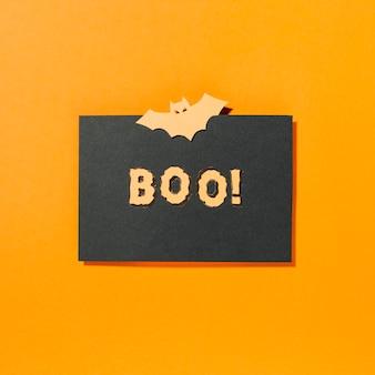 Boo! inschrift und fledermaus auf schwarzem papier in der mitte