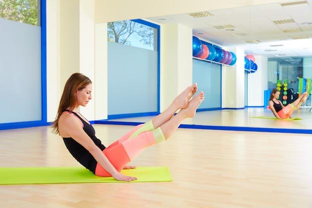 Boomerang-übungstraining der pilates-frau an der turnhalle