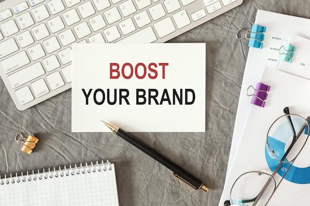 Boost your brand steht in einem dokument mit bürozubehör auf dem schreibtisch.