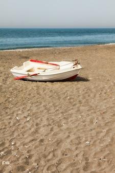 Boot am strand skyline ein kleines holzboot, das von fischern benutzt wird, die am sandstrand neben dem mittelmeer gestrandet sind