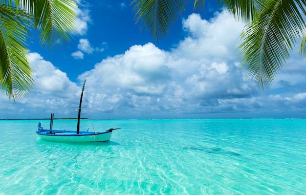 Boot am tropischen strand am sonnigen tag