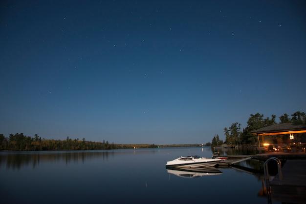 Boot an einem dock, kenora, see des holzes, ontario, kanada