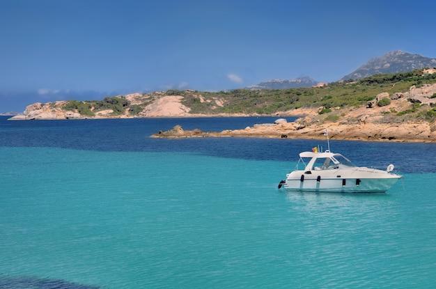Boot auf dem türkisfarbenen meer nahe korsika-küste