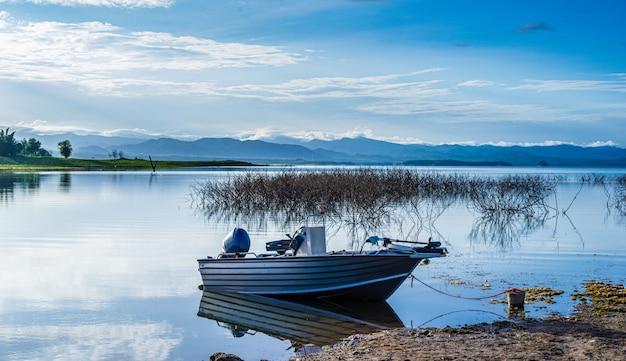 Boot auf einem gebirgssee mit sonnenlicht natürlicher verdammungssee im wald.