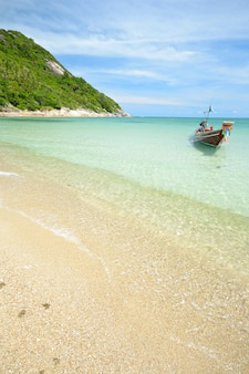 Boot, das auf transparentes wasser, tropisches strandtürkismeer in thailand schwimmt