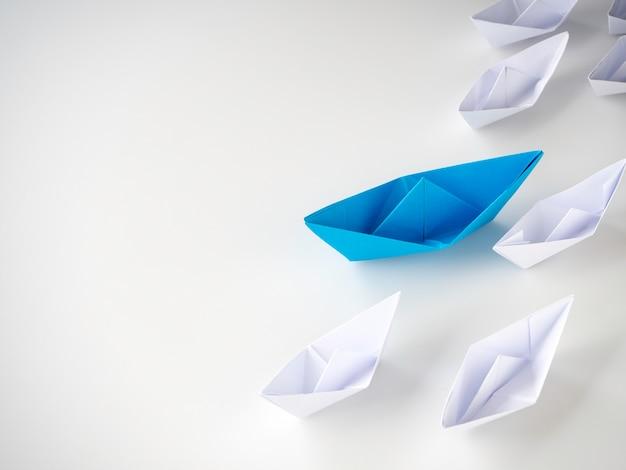 Boot des blauen papiers, das unter weißen schiffen führt