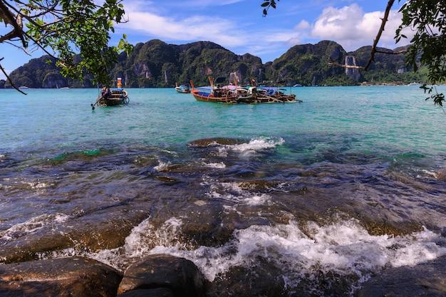 Boot des langen schwanzes auf dem sand im meer an hochsaison-sommerferien der phi phi-insel