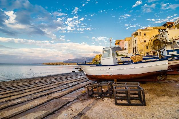 Boot in einem kleinen hafen in einem fischerdorf an der küste von sizilien angedockt.