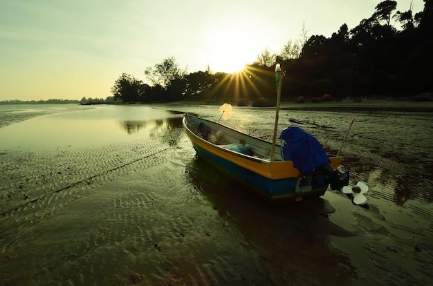 Boot in strandnähe, wenn die sonne untergeht