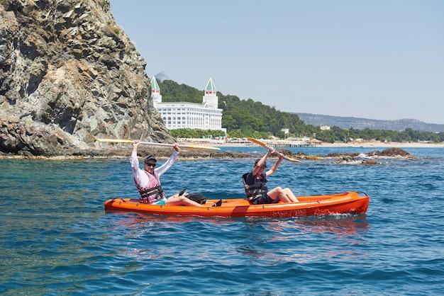 Boot kajakfahren in der nähe von klippen an einem sonnigen tag. kajak fahren in einer ruhigen bucht. erstaunliche aussichten. reise-, sportkonzept. lebensstil. eine glückliche familie.