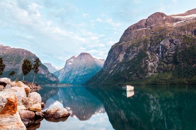 Boot koppelte im ruhigen see einer träumerischen landschaft mit schönem berg an