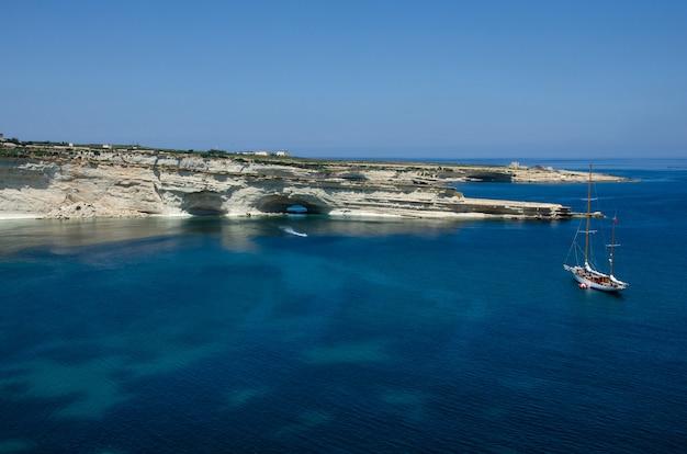 Boot nahe weißen felsen mit blauem wasser in malta nahe marsaxlokk, heiliges peter pool. munxar-pfad