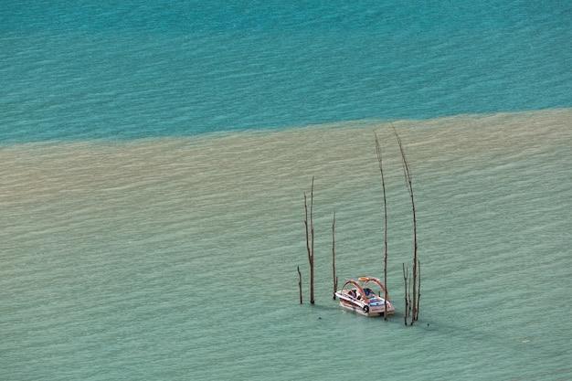 Boot türkisfarbenes wasser des bergsees überflutete bäume