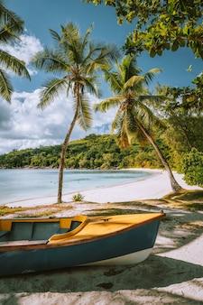 Boote am exotischen strand takamaka mit palmen und blauer ozeanlagune, insel mahe, seychellen.