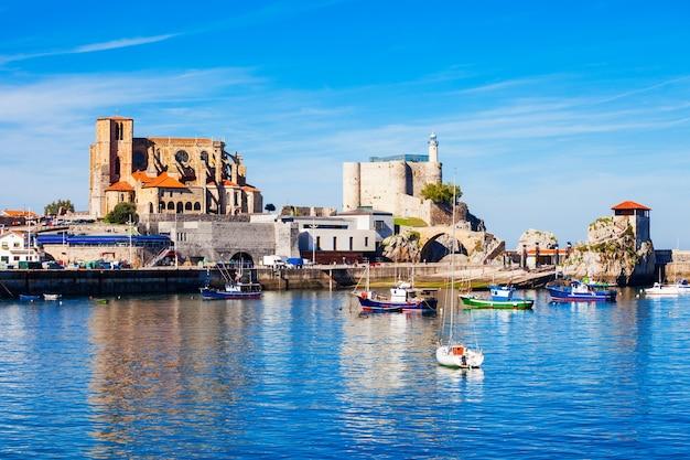 Boote im hafen von castro urdiales, der kirche santa maria und dem leuchtturm der burg santa ana in der region kantabrien im norden spaniens.