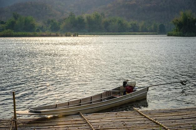 Boote koppelten auf einem gebirgssee mit sonnenlicht an natürlicher verdammungssee im wald.