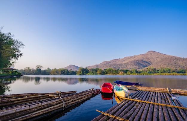 Boote und floß auf einem gebirgssee mit sonnenlicht. natürlicher dammsee im wald.