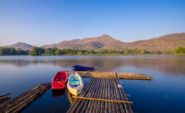 Boote und floß auf einem gebirgssee mit sonnenlicht.