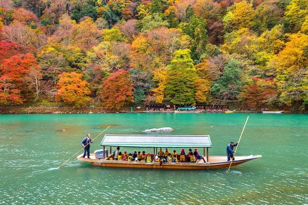Bootsmann, der das boot am fluss stochert. arashiyama in der herbstsaison entlang des flusses in kyoto, japan.