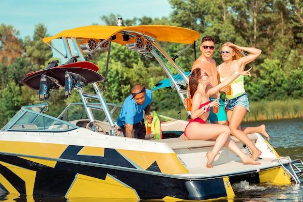 Bootsparty. dunkelhaariges mädchen mit einer flasche in der hand sitzt auf einer yacht neben ihren freunden und zeigt in die ferne
