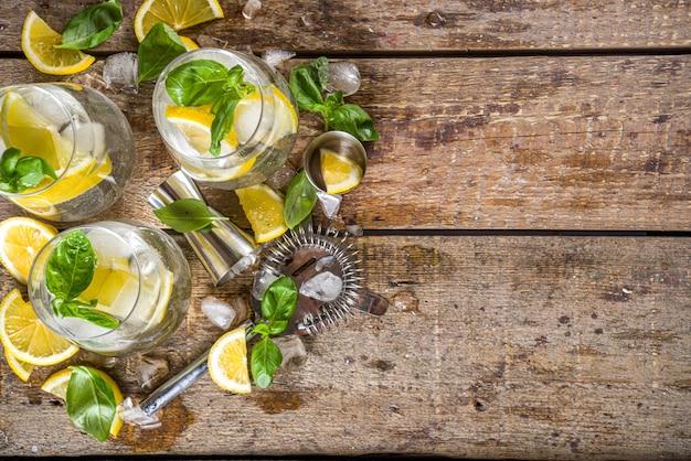 Boozy zitronen-basilikum-limonade, mit frischen basilikumblättern, zitronen und zerstoßenem eis, rustikaler holzhintergrund-kopierraum