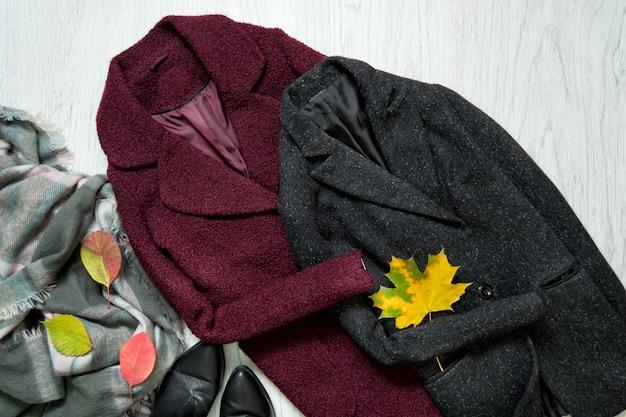 Bordeauxrote und graue mäntel, schal, schwarze schuhe und herbstlaub. modisch