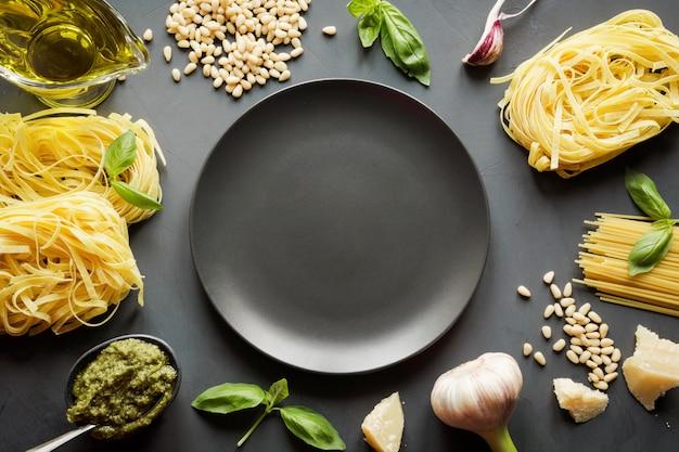Border von rohen nudeln, pesto, basilikum, parmesan zum kochen mediterraner gerichte.