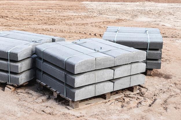 Bordsteine in einer packung. bordstein vorbereitet für die verlegung auf der baustelle. straßenarbeiten.