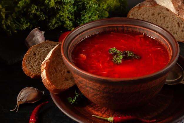 Borsch - rote-bete-suppe in einer tonschale auf einem steinhintergrund, traditionelles gericht der ukrainischen küche.