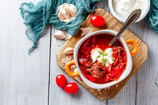 Borsch traditionelle ukrainische und russische suppe mit fleisch, rüben und kohl. fleischsuppe in einer orangefarbenen schüssel.