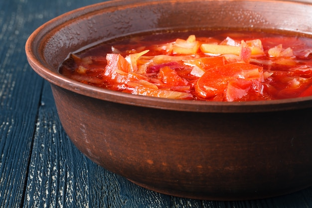 Borscht rote-bete-suppe auf dem tisch mit scheiben roggen-müsli-brot und sauerrahm. rustikaler stil
