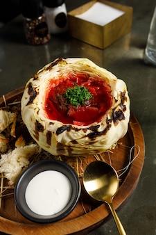 Borschtsch mit kalbsbäckchen in gebratenem kohl