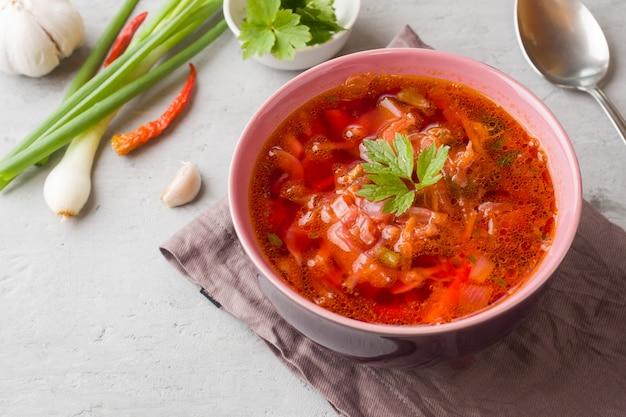 Borschtsch, rote-bete-wurzeln suppe in einer holzschale mit frischen kräutern