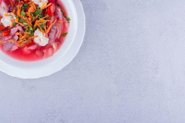 Borschtsch-suppe mit karotten- und blumenkohl-topping auf marmorhintergrund. foto in hoher qualität
