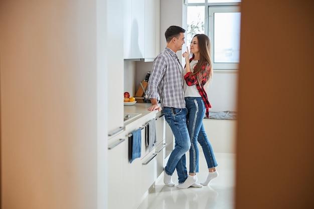 Boshafte frau neckt ihren mann in der küche