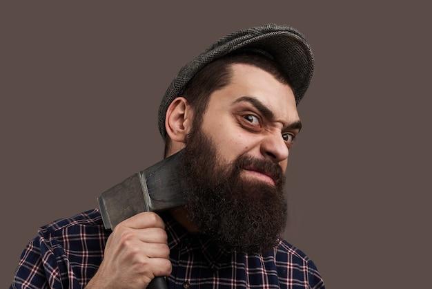 Boshafter brutaler bärtiger mann, der sich mit axt rasiert. porträt des hipsters mit bart. heißes männliches konzept. verrückte emotionen im gesicht.