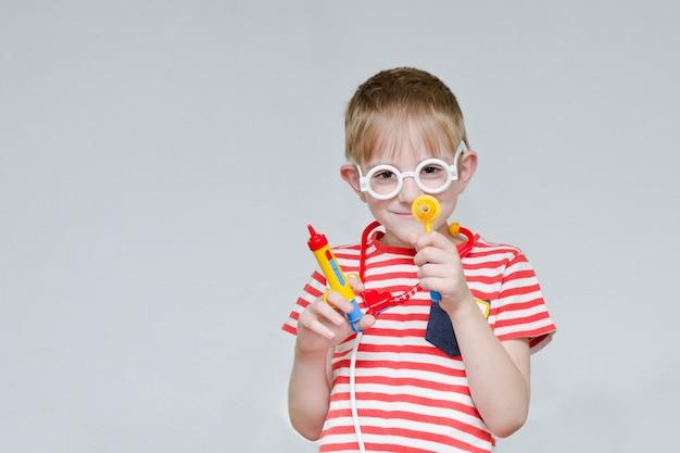 Boshafter junge, der doktor spielt. spielzeugspritze, brille und phonendoskop. porträt