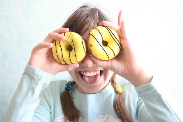 Boshaftes jugendlich mädchen mit zwei zöpfen, die zwei schaumgummiringe mit gelber zuckerglasur nahe den augen halten, zunge lächeln und zeigen.