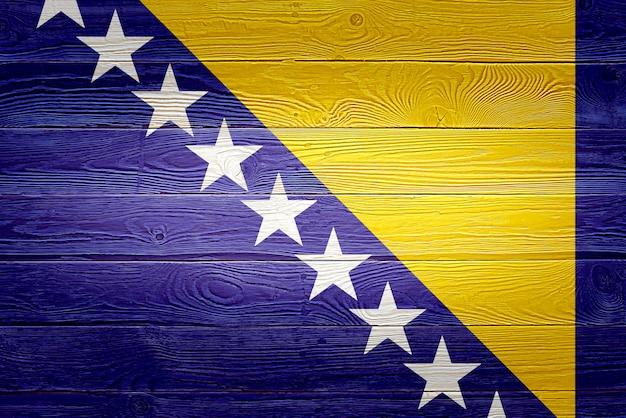 Bosnien und herzegowina flagge gemalt auf altem holzbretthintergrund