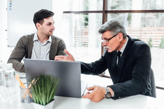 Boss mit seinen neuen mitarbeitern im modernen büro, die über präsentation mit laptop sprechen.