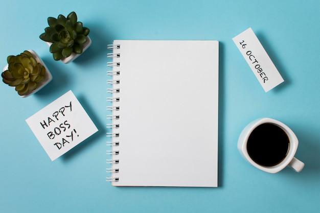 Boss tageskomposition auf blauem hintergrund mit leerem notizblock