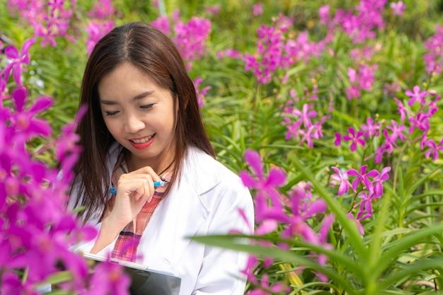 Botanische forschungsorchidee des glücklichen forschers, die eine weiße kappe trägt