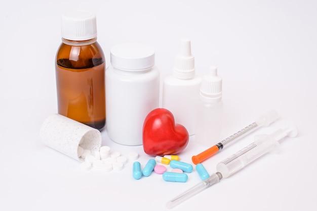 Botox schönheit kollagen ohren augen tropfen steriles kleines angriffskonzept. schließen sie herauf foto von vielen satzbehältern mit pillen und drogen geteilt fallen auf tischspritzen isoliert