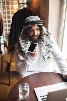 Botschaft. arabischer geschäftsmann, der im büro arbeitet, geschäftszentrum mit gerät, gadget. moderner saudischer lebensstil. mann in traditioneller kleidung und schal sieht selbstbewusst, beschäftigt, gutaussehend aus. ethnizität, finanzen.