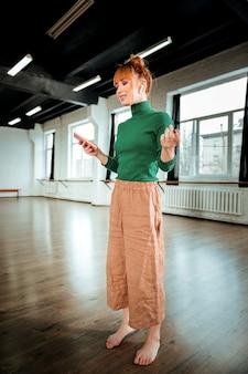 Botschaft. rothaariger professioneller yogalehrer, der einen grünen rollkragenpullover trägt, der eine nachricht liest