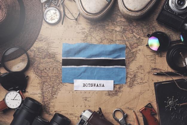 Botswana-flagge zwischen dem zubehör des reisenden auf alter weinlese-karte. obenliegender schuss