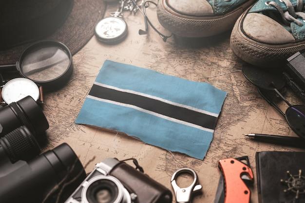 Botswana-flagge zwischen dem zubehör des reisenden auf alter weinlese-karte. touristisches bestimmungsort-konzept.