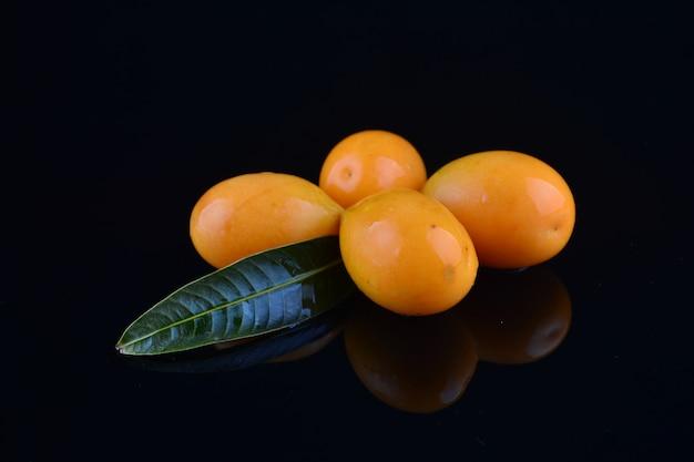 Bouea oppositifolia, exotische frucht auf schwarzem hintergrund isoliert