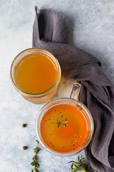 Bouillon mit knochen- oder gemüsebrühe in einem glasbecher und aromatischen kräutern